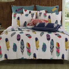 Colorful feathers billow on the breeze in the Dream Catcher  Bonus quilt set. Let the Western wind summon the peaceful spirits of slumber. Face print features red, crocus, blue, gold, teal and gray pinions on an ivory ground. Wind-swirl quilting throughout. Reverses to a coordinate feather print on teal blue for two looks in one!  Oversized for better coverage on today's deeper mattresses.  Prewashed and preshrunk. Machine quilted with fabric bound edges for durability and surface interest…