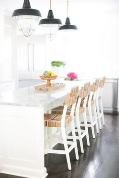 White center island seats four seagrass counter stools on dark stained oak floors in front of a white island topped with a gray quartzite countertop illuminated by three Thomas O'Brien Henry Industrial Hanging 2 Light Pendants.