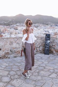 Leonie Sophie keeps it simple in a white bell sleeved off the shoulder top, paired with linen culottes and a pair of patterned sneakers. This style is perfect for eveningwear on holiday, or just a warm evening at home! Trousers: Marc'o Polo, Bag:...
