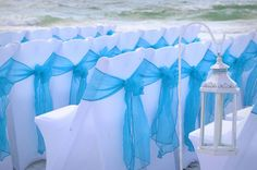 Turquoise sashes bring a rich color against white chair covers