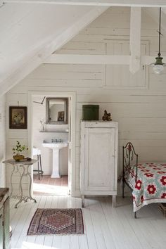 Adorable cabin\cottage whitewashed walls and wood floors painted white. Vintage quilt.