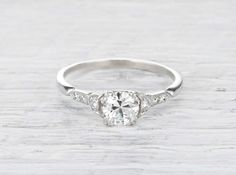 Antique Art Deco engagement ring made in platinum and centered with an EGL certified approximately .70 carat old European cut diamond with F color and VS2 clarity. Signed J.E. Caldwell. Circa 1925.