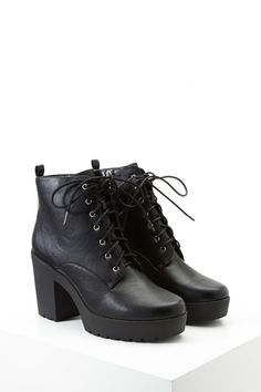 A pair of faux leather booties featuring a lace-up top, block heel, ridged platform, side zipper, high-polish grommets, and a pull tab.