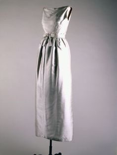 """Blue Evening Dress Maker: Chez Ninon (American, est. 1927) Date(s) of Materials: 1961 Medium: Silk shantung Dimensions: 49"""" center back Description: An evening dress with belt in ice blue silk shantung. (after spring-summer model number 3390 by Hubert Givenchy). This is Chez Ninon's freehand interpretation of a Givenchy dress. The belt, decorated with a bow, cinches the dress to create pleats at the waist. Historical Note: This dress was worn by Jacqueline Kennedy to dinner with Queen…"""