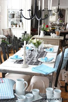 A Swedish diningroom is a bit cheerier with aqua napkins and pillows.