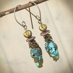 From the New Tribe Chic collection, handmade polymer meteor cones in gradient shades of olivine are highlighted with turquoise caverns. Your meteors are paired with antiqued bronze wire wraps, tribal copper spools and pale olive pearls. Topped off with handmade non-allergenic Titanium earwires. Titanium is nickel and lead free. These earrings are as light as []