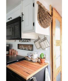 Place a magnetic strip with spice jars in the space above the stove and a small photo in the space next to the sink