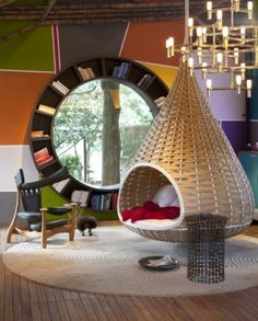Circles and curves abound in the living room, with the suspended nest chair's circular base, a round jute rug, the Chifruda chair's parabolic headrest and Galeazzo's original creation, an orbital bookshelf window.