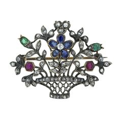 Victorian flower basket motif pin set with rose cut diamonds, sapphires, rubies and emeralds.