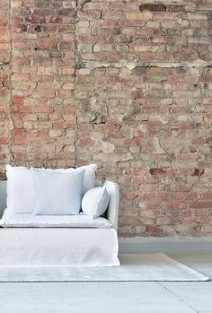 white linen sofa | red brick wall | modern living room decor | ghost gervasoni sofa | IKEA Söderhamn sofa with a Bemz Loose Fit cover in white linen