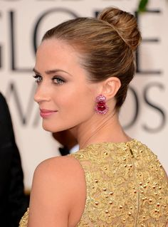 Emily Blunt wearing smudged bronzed shadow on upper lids, softly defined lower lash line, highlighted bronzed skin, peach cheeks and a pop of pink satin lips