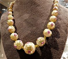 ITEM # 21704  This is a stunning statement Art Deco, circa 1920s-30s Venetian wedding cake beaded Murano lampwork with applied fiorato pink roses and gold. My camera does not do this piece justice. The beads are all hand created and strung, graduating from 8mm all the way up to the center bead measuring 20mm in diameter. There are two glass spacer beads between each bead. Necklace has a barrel clasp and measures 19 in length.  Very good antique condition with typical wear due to age and…