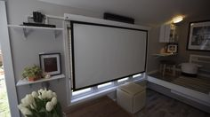 Tim and Shannon's tiny house -- This retractable screen, paired with an HD projector and surround sound, provides a great entertainment solution with no wasted space.
