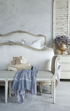 Beautiful French love seat, with whitewashed furnishings and lavender-hued accents.