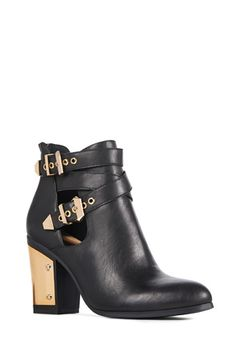Cutout and so cool, this bootie features dual crossed straps with metallic hardware and a bold metallic plate on the heel. Faux leather.