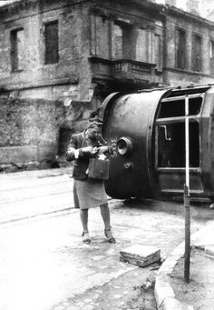 Polish resistance nurse of the Polish Home Army stands in front of an overturned tram  during Uprising. 200,000 Polish civilians not involved w/ the resistance died, mostly from bombings, fire, mass executions. During the urban combat, approximately 25% of Warsaw's buildings were destroyed. Following the surrender of Polish resistance German troops leveled another 35% of the city block by block.