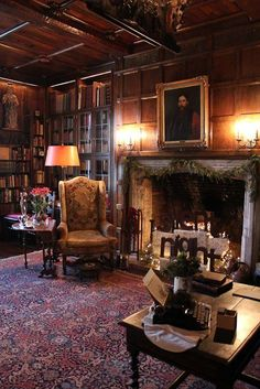 Dark panelled wood library with large mantel and red accents.