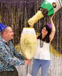 Grab a giant champagne bottle and champagne glass balloon for brilliant New Year's Eve photo booth props! (And find out how to make this DIY glitter backdrop on our blog!)