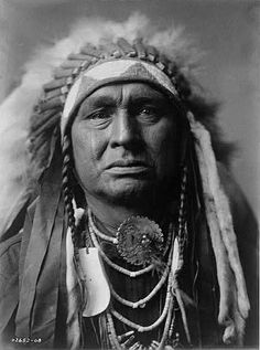 White Man Runs Him (Maschidit-kudush) (c. 1858-1929) - Crow -  Also known as White Buffalo That Turns Around, he was born into the Big Lodge Clan of the Crow Nation, the son of Bull Chief and Offers Her Red Cloth. At the age of about 18, he volunteered to serve as a scout with the United States Army on April 10, 1876, in its campaign against the Sioux and Northern Cheyenne, traditional enemies of the Crow. - Photo by Edward S. Curtis, c. 1908. (B&W copy)
