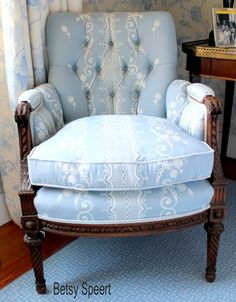 Louis XVI bergere (a French style closed arm club chair with a partially exposed wooden frame) upholstered in a pretty blue and white fabric by Scalamandre.