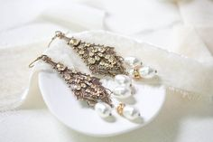 If you are fascinated with the timeless beauty of vintage jewelry, this pair of chandelier wedding earrings in antique gold with Swarovski crystals is precisely what you are looking for. Because of their chandelier design, they will look absolutely amazing paired with a braided or curly-haired up-do. Moreover, their unique antique gold finish will flawlessly complement a lacy wedding gown with vintage accents. Swarovski Crystal Earrings, Ivory Pearl, Wedding Earrings, Chandelier Earrings, Chandelier Wedding, Antique Gold, Bridal Jewelry, Vintage Jewelry, Timeless Beauty