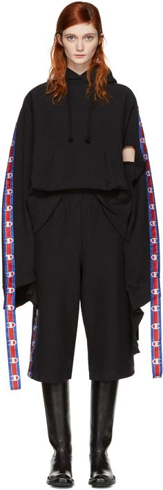 Long sleeve French terry hoodie in black. Logo patch and drawstring at hood. Kangaroo pocket at waist. Vent at armscyes. Textile logo tape in red, white, and blue at overlong sleeves and back yoke. Rib knit cuffs and hem. Creasing at front hem. Panels at cuffs and back hem. Tonal stitching.   Part of the Vetements x Champion collaboration.