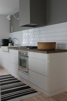 Love these kitchen cabinets because they have no handles and they're all white.  Love the timber bench tops. NOt sure about the grey top half of wall above splash back.