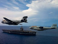 Two EA-6B Prowlers assigned to the Rooks of Electronic Attack Squadron (VAQ) 137 fly in formation over the aircraft carrier USS Enterprise (CVN 65).