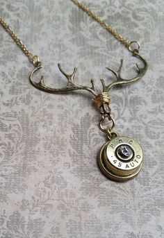 This bullet deer necklace was created with antique gold antlers and a brass, spent .45 caliber bullet casing. There is a 6mm crystal in the center of the casing.This necklace is perfect for a lady that likes hunting or for a country girl.  Antlers are 1 3/4 across Pendant is 1 3/4 long Chain is 18 Lobster claw closure   Check out more of our bullet jewelry on Etsy here: https://www.etsy.com/shop/RepurposedRelicsTX?section_id=16687149&ref=shopsection_leftnav_3  -This necklace comes in a gift…