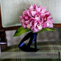 A compactly gathered bouquet of individual pink cymbidium orchid blossoms, wrapped in navy double faced satin ribbon