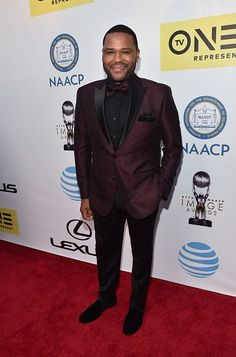 Anthony Anderson in a maroon tuxedo jacket with black lapels and a bowtie at the NAACP Image Awards at Pasadena Civic Auditorium in Pasadena, California. Maroon Suit, Maroon Tuxedo, Triangle Face Hairstyles, Suits For Guys, Male Face Shapes, Celebrity Hair Stylist, Celebrity Guys, Black Sparkly Dress, Anthony Anderson