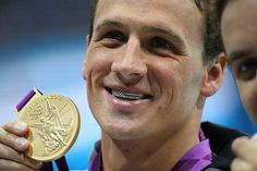 Olympic gold medalist Ryan Lochte shows off his American flag grills and gold medal after winning the Men's 400m Individual Medley for the U.S. at the London 2012 Olympics Aquatic Center.
