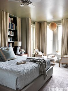 In a Washington, D.C., house designed by Barry Dixon, flax curtains cocoon the bedroom and hide all the books. A round beaded Coco lantern by Four Hands draws attention to the tall ceiling and illuminates the reading nook, furnished with Zentique chairs and ottoman. Upper East coverlet from Ankasa.   - HouseBeautiful.com