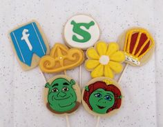 Shrek themed Sugar cookies decorated with Royal icing. Shrek, Fiona, farquaad crown and flag banner, along with a yellow flower and the Shrek Logo! So fun!