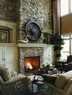 I really like how the color palette used throughout the room and the fireplace match.  The fireplace rock is carried on to the walls to give the room a grand decorative impression.