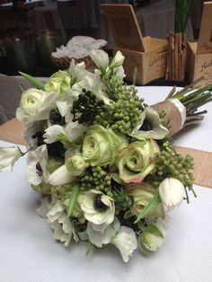 Jade roses, green hydrangea, white anemone, berzilla berry and assorted spring blossoms, wrapped in rustic burlap
