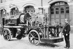 Self propelled German Fire Engine with man in uniform next to it.