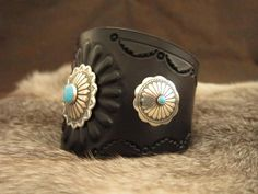 DIABLO  Black leather,  2 1/4 inch wide at it's widest. Fully lined, hand stamped, dyed and finished, with sterling silver and turquoise conchos from Sunwest Silver in Albuquerque, NM.  Fits a 6 to 7 inch wrist and closes with an adjustable button stud closure.  $99.00  www.stonesriverleather.com
