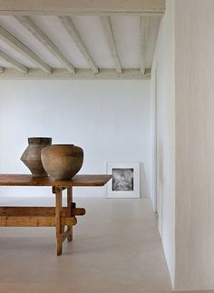 simple interior designed by AXEL VERVOORDT .Calvin Klein's home in Miami, Florida. Old wooden dinning table, beamed ceiling, concrete floor. featured in 'Est Magazine'