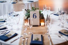 White table with burlap (or butcher paper) runner, navy blue napkins, and greenery (add white flowers?)