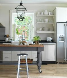 Gray painted island with wood top, open shelves, lantern...