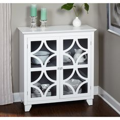 Add a elegant look to any room with this stylish and unique white exterior and grey interior finished cabinet. The eye-catching cabinet features two tempered glass doors with scrolled details and lots of room for storage.