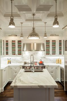 Exquisite kitchen with polished nickel picture lights illuminating glass-front upper cabinets and inset lower cabinets paired with white and grey marble countertops and white marble backsplash.