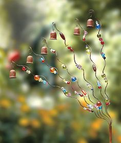 Fill your outdoors with the wild look and charming melodies of the Twisted Garden Bell Tree. has 6 spiral wires adorned with multicolored acrylic beads and bells at the tips. When the wind blows