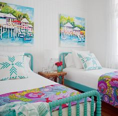 Crisp white walls set a blank slate for this colorful Tybee Island bedroom. The bright, azure beds (from The Land of Nod) meld perfectly with beachy art by Bellamy Murphy. The fun graphic pillows and blankets (from Celadon) add further depth to the room's