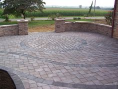circle pattern within paver patio & walls that double as benches. pillars at the side of the entry can be planters.