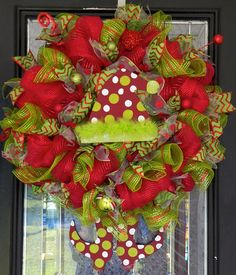 This Elf Themed Christmas Wreath is made with layered loops of metallic red deco mesh and accented with a Christmas themed deco mesh, custom