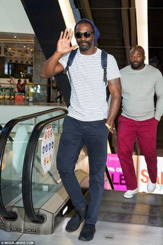 Looking buff! British actor Idris Elba (L) gave his Thor co-star Chris Hemsworth a run for his money on Monday when he showed off his muscly arms in a T-shirt during a store appearance