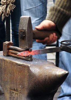 blacksmith shapes an iron bar