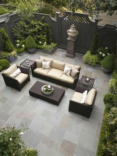 Beautiful outdoor livingroom with lattice fence and topiaries.